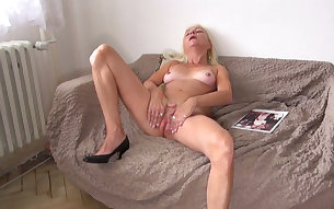 Beautiful and elegant blonde granny shows her pussy on the couch