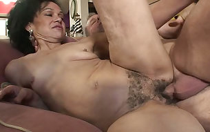 Outrageously wild sex of a mature couple on the couch