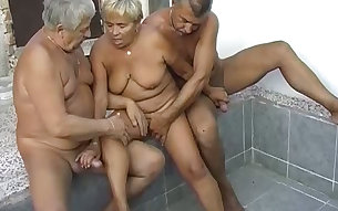 Trashy looking short haired granny fondles with two geezers in 3 some