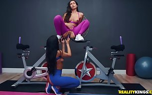 Lesbians in torn workout pants toy fucking in the gym