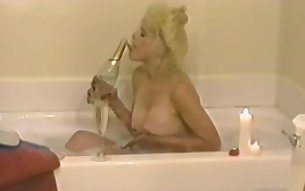 Amateur blonde mature fucks herself with a big black dildo while laying in bed