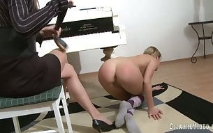 Piano teacher punishes her student and fucks her with a strap on dildo
